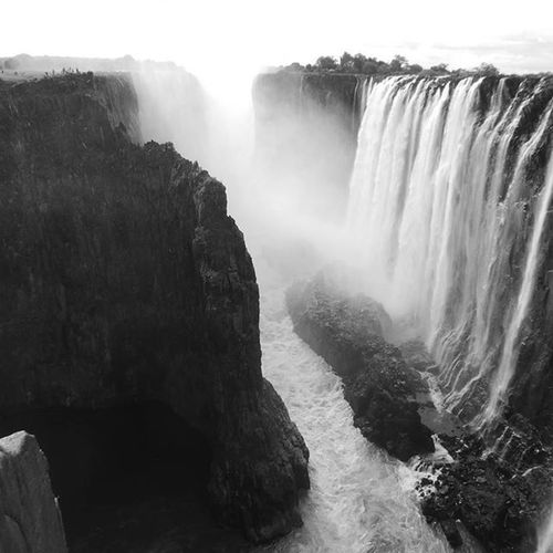 "Another one from Victoria falls a few weeks ago. Mosi oa tunya, The Smoke That Thunders. There was plenty of ""smoke"" when I was there and apparently the waters were quite low. Some day I'll have to come back to see it in full force. Its over 100m high and a mile wide. If you want some scale, look for the people on top of the cliff in the top left corner. Vicfalls MosiOaTunya Victoriafalls falls Zambia Zimbabwe Blackandwhite @victoriafallsphotos"