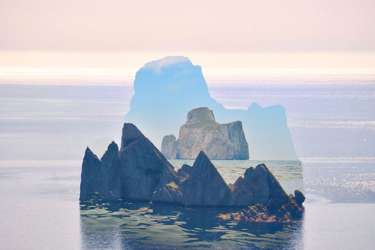 Double exposure of rocks in sea against sky during sunset