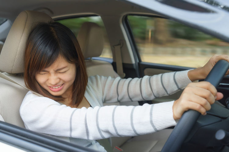 Scared Young Woman Driving Car