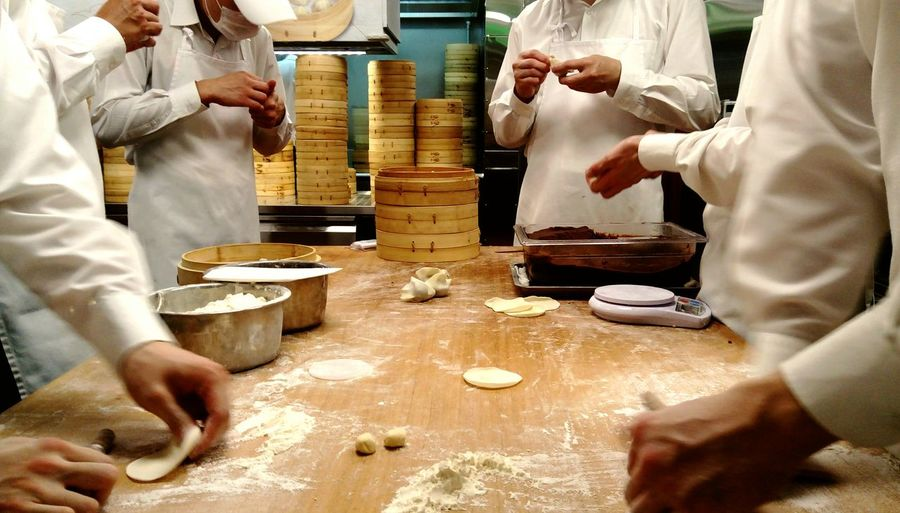 Chefs Making Dumplings In Kitchen