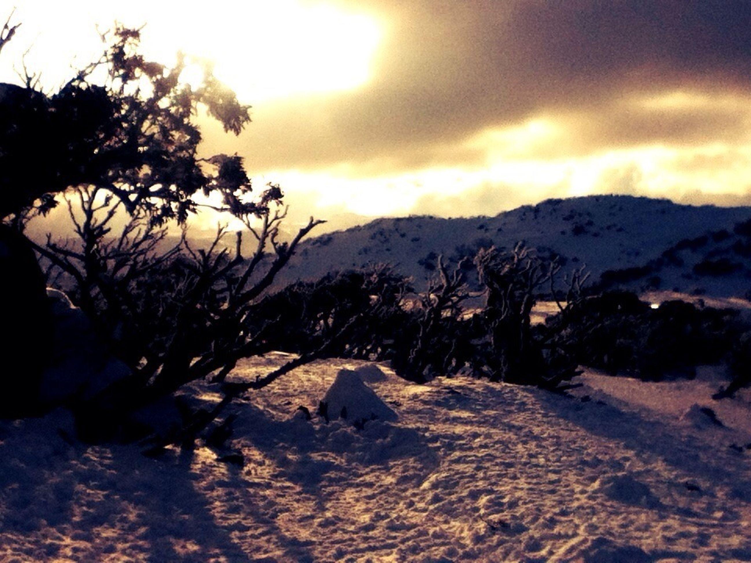 mountain, tranquil scene, sky, tranquility, scenics, beauty in nature, sunset, landscape, nature, mountain range, cloud - sky, tree, non-urban scene, sun, sunlight, idyllic, cloud, rock - object, remote, snow
