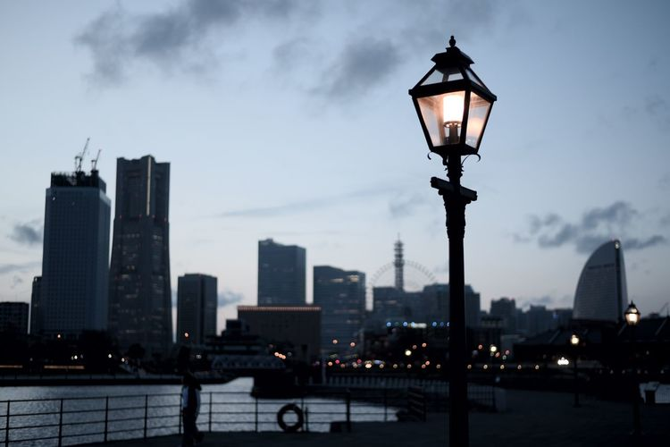 Illuminated street light by buildings against sky
