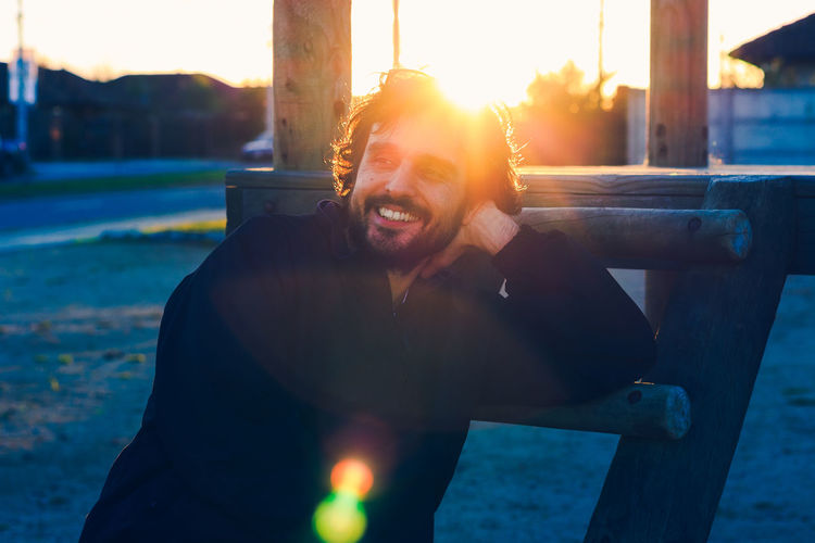 Happy young man sitting against sky during sunset