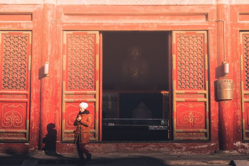 Full length of man standing by red door of building