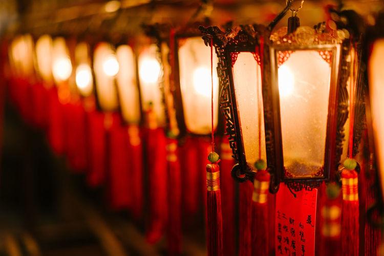 Close-up of illuminated lanterns hanging in row