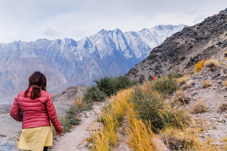Woman walking along the track at passu glacier in karakoram mountain range, pakistan.
