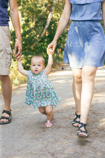 EyeEmNewHere Casual Clothing Childhood Daughter Day Eye4photography  Family Family With One Child Father Front View Full Length Girls Holding Hands Leisure Activity Lifestyles Love Low Section Mother Outdoors Real People Standing Summer Three People Togetherness Walking