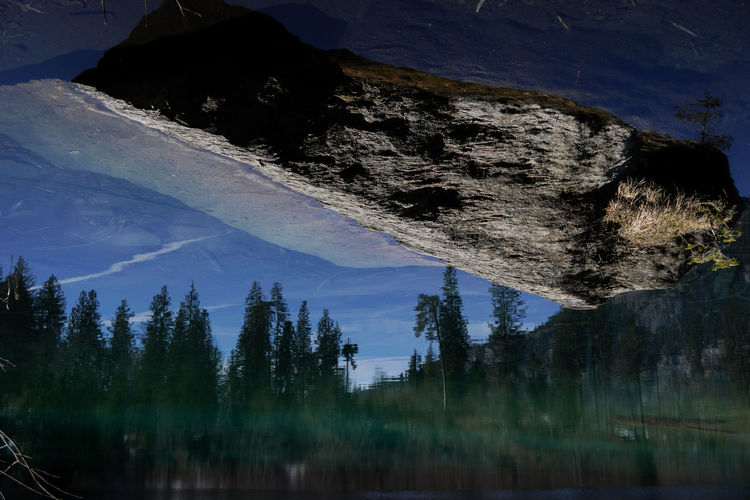 Panoramic shot of trees reflecting in lake cresta against sky