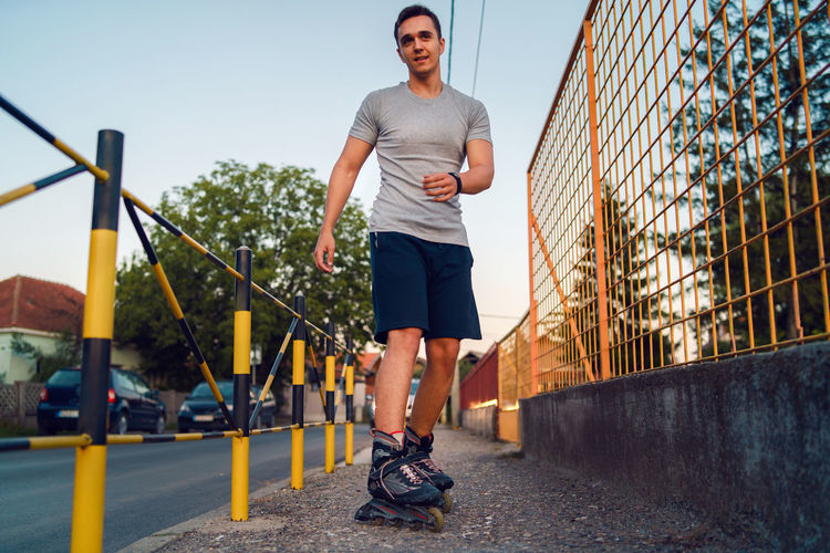 Full length of young man standing with roller skates on footpath