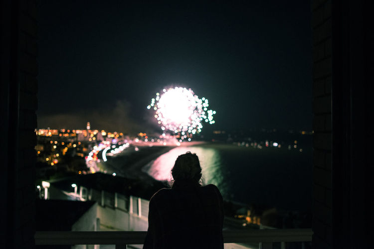 Fireworks in front of the sea Night Illuminated Rear View Architecture City Real People Building Exterior Built Structure One Person Sky Standing Leisure Activity Adult Silhouette Waist Up Outdoors Arts Culture And Entertainment Lifestyles City Life Cityscape Watching Looking At View