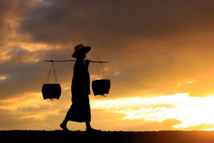 Low angle view of silhouette clothes hanging on land against sky during sunset