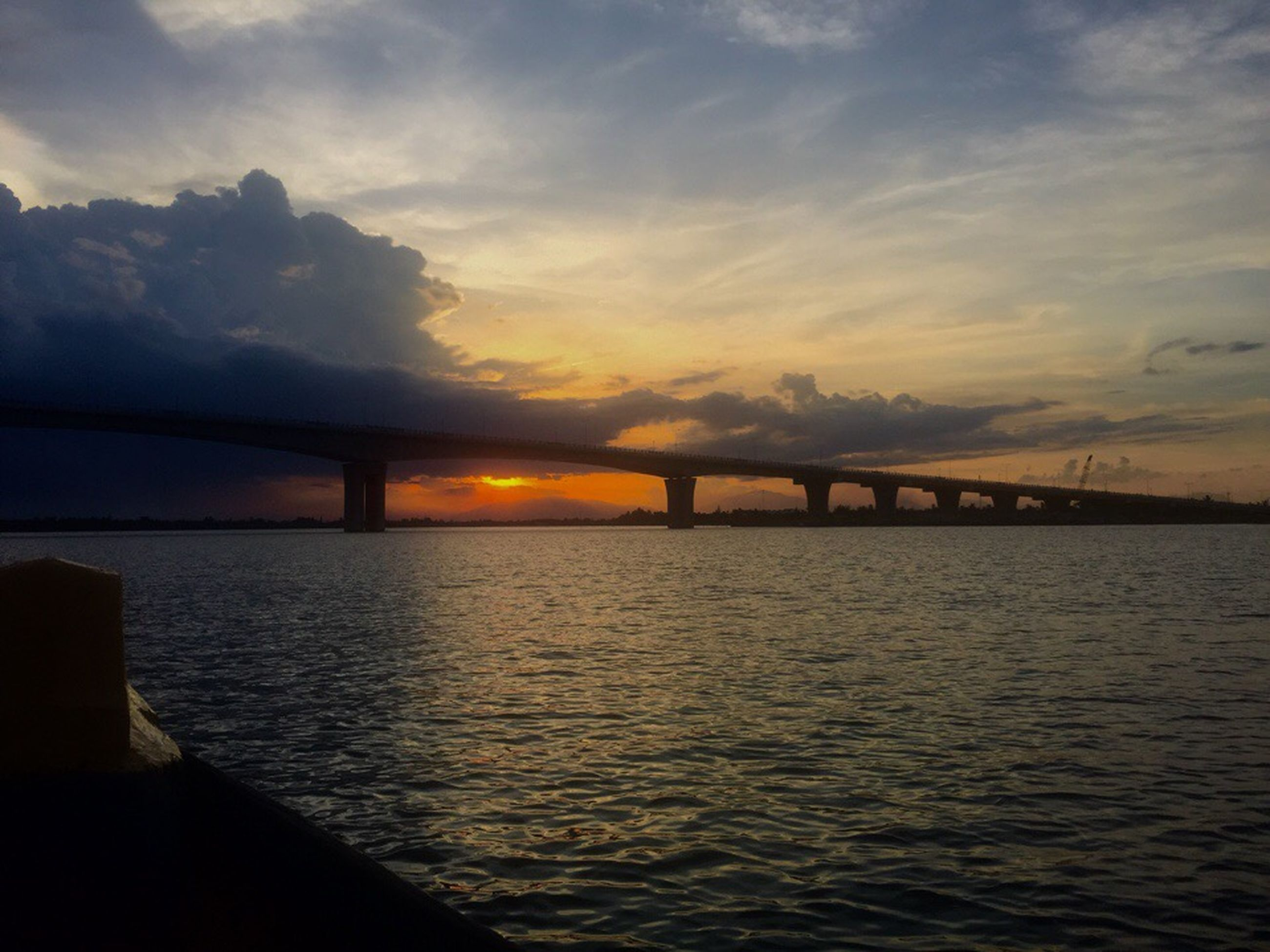sunset, water, sky, built structure, silhouette, architecture, connection, bridge - man made structure, waterfront, tranquil scene, tranquility, scenics, river, beauty in nature, cloud - sky, nature, reflection, bridge, sun, orange color