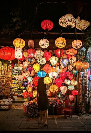 Woman buying illuminated lanterns hanging on street at night