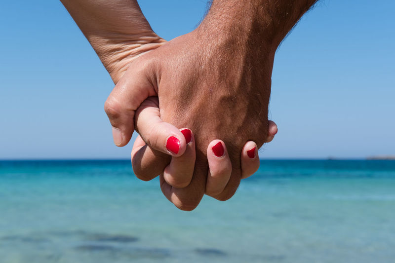 Cropped image of couple holding hands against sea