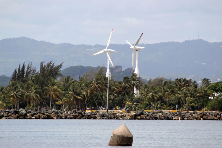 Windmills by lake against sky