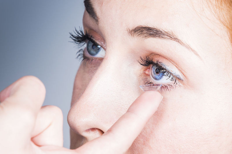 Close-up of woman applying contact lens