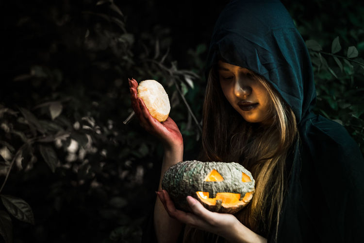 Woman in witch costume holding illuminated jack o lantern by plants during night
