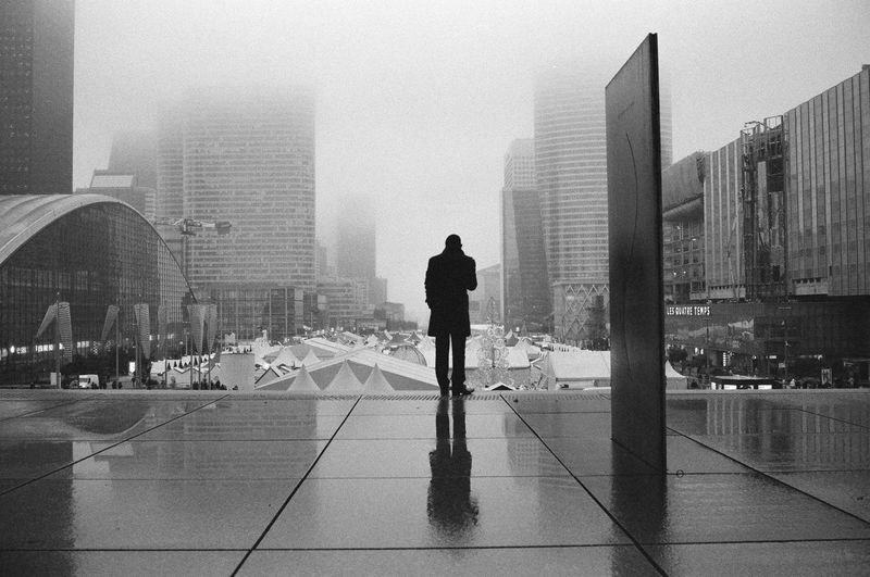 Man walking on modern cityscape against clear sky
