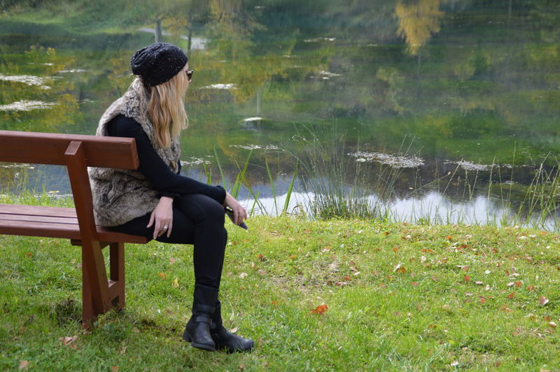Side view full length of woman sitting on bench at grassy field