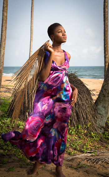 Thoughtful woman holding palm leaves while standing on shore at beach