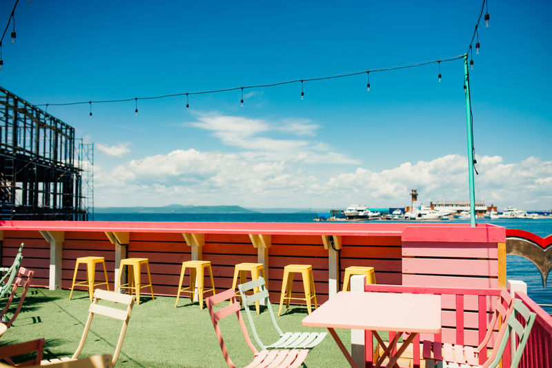 Empty chairs and tables by sea against blue sky