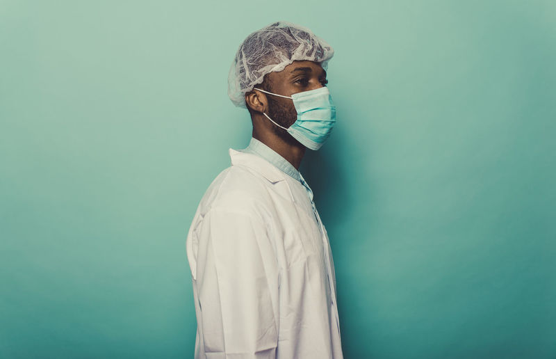 Doctor wearing mask standing against blue background