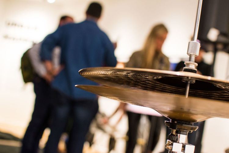 Close-up of cymbals with people in background