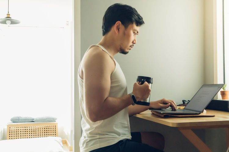 Young man using mobile phone at home