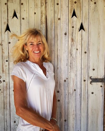 Portrait of smiling mature woman standing by wooden wall
