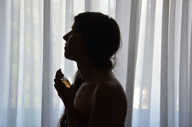Contemplation Curtain Domestic Room Headshot Leisure Activity Lifestyles Long Hair Perfume Silhouette Woman Young Adult