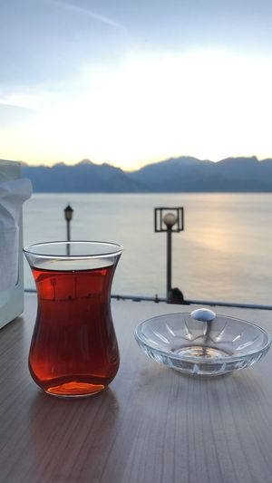 Close-up of drink on table by lake against sky during sunset