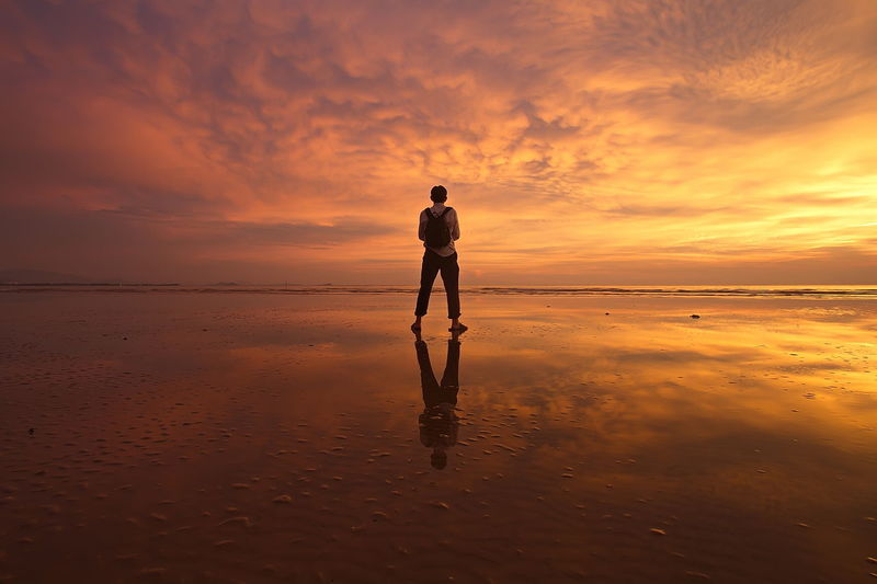 Rear view of man on beach against dramatic sky