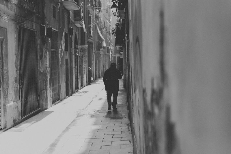 Rear View Of Man Walking In Narrow Street