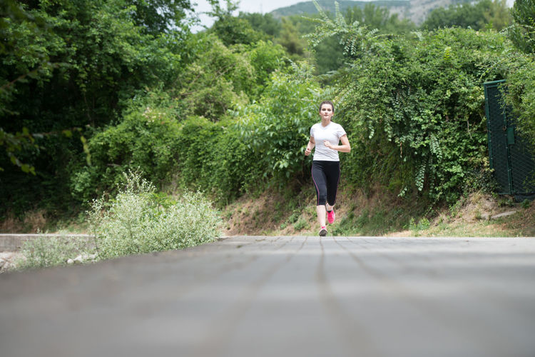 Woman running on road amidst trees