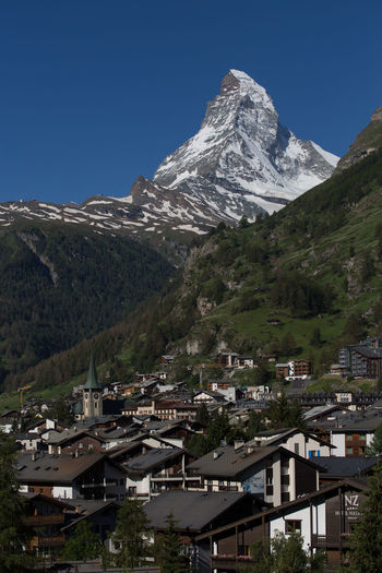 The Matterhorn, rising above the town of Zermatt, Switzerland Copy Space Matterhorn  Architecture Beauty In Nature Building Building Exterior Built Structure City Clear Sky Cold Temperature Day Environment Landscape Mountain Mountain Peak Nature No People Outdoors Residential District Scenics - Nature Sky Snow Snowcapped Mountain Summer Zermatt Switzerland