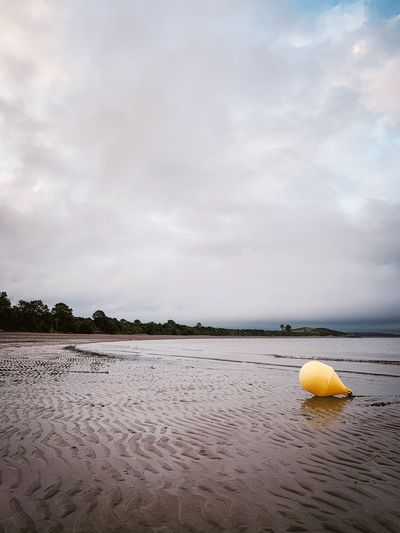 Yellow floating on beach against sky