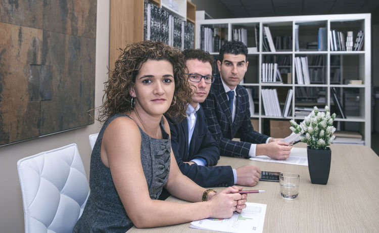 Executive team sitting at the negotiating table in headquarters Business Company Horizontal Man Office Teamwork Woman Working Workplace Business Finance And Industry Businessman Businesswoman Caucasian Chairman Chief Female Headquarters Male People Portrait Professional Seriousface Sucess Team Three People