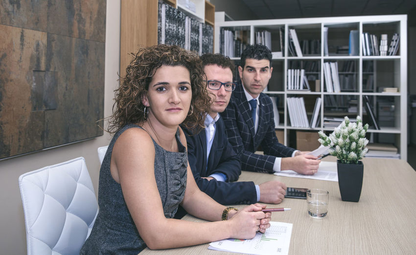 Portrait Of Business People Sitting At Desk In Office