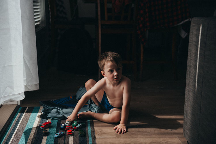 Cute shirtless boy playing with toy cars while sitting on floor at home