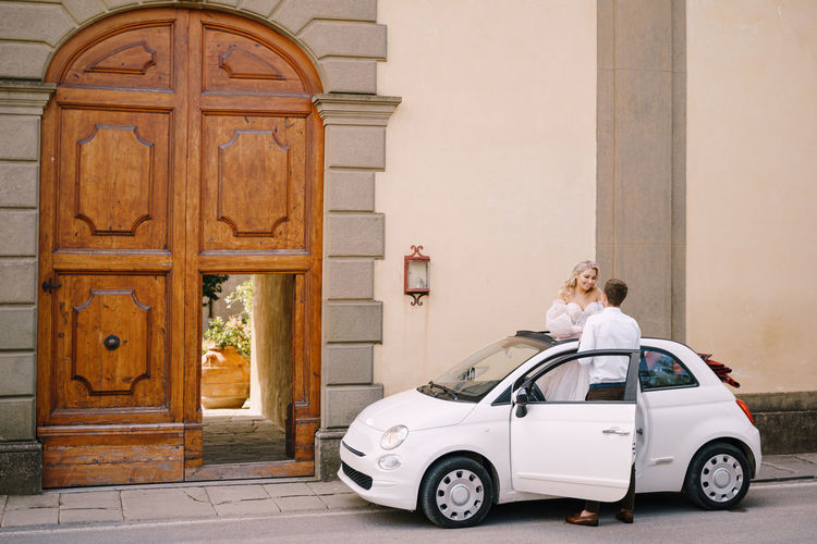 Rear view of woman standing by door of building