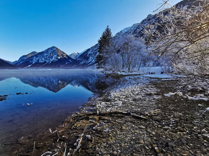 Scenic view of lake by snowcapped mountains against clear sky