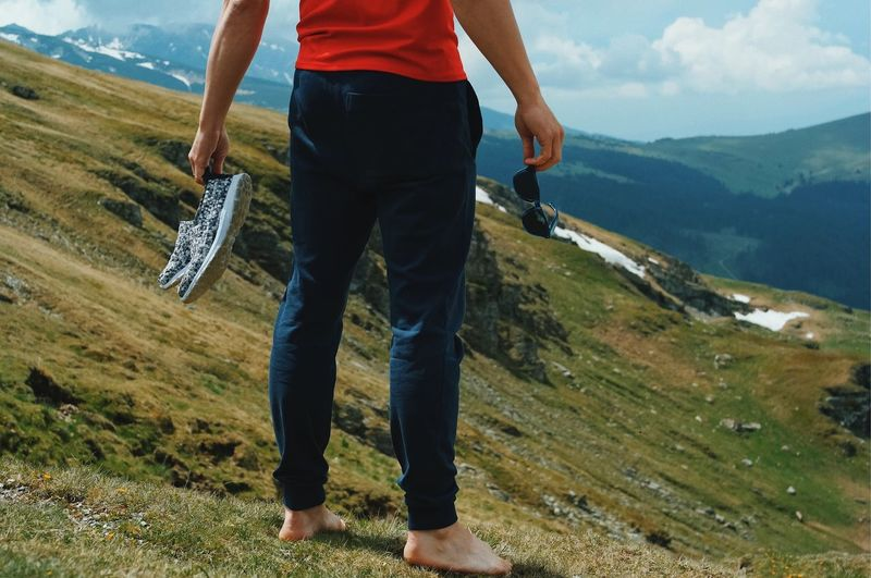 Low section of man standing on mountain