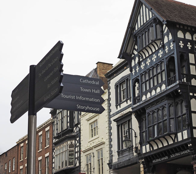 Architecture City Sky Day Outdoors Street Signs Text Clear Sky Communication Close-up No People Low Angle View Building Exterior Built Structure Western Script Elizabethan Architecture Direction Signs A Taste Of Chester, UK Glorious Cheter