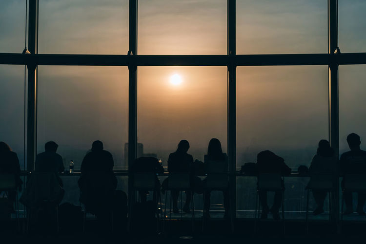 Silhouette people sitting by glass window at sunset