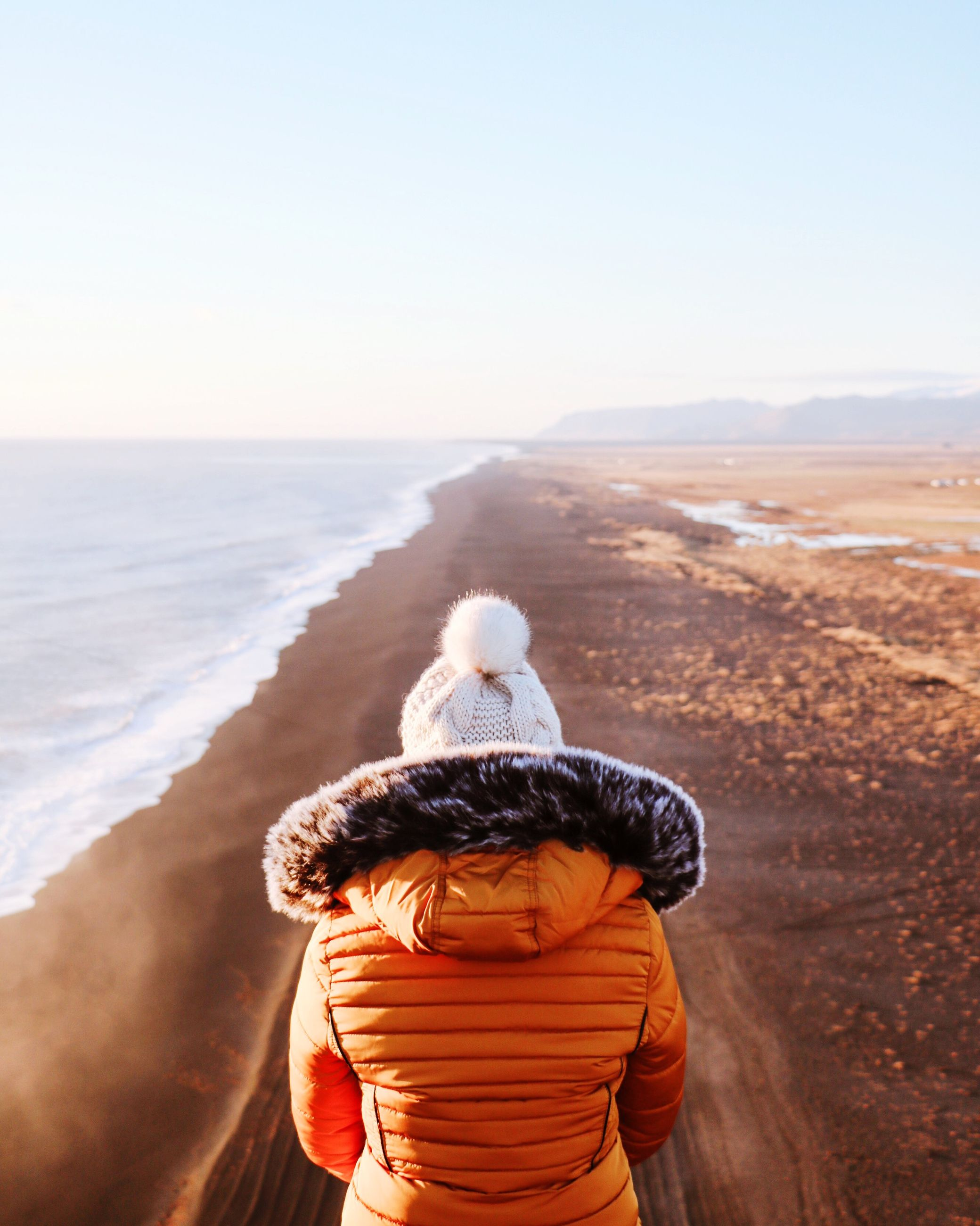 rear view, sea, real people, sky, land, lifestyles, leisure activity, one person, beach, beauty in nature, water, clothing, scenics - nature, nature, hat, day, waist up, women, horizon over water, outdoors, warm clothing, hood - clothing, looking at view