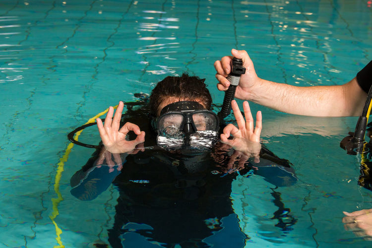 Instructor assisting woman in scuba diving in swimming pool