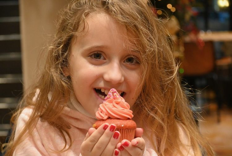 Portrait of girl eating cupcake