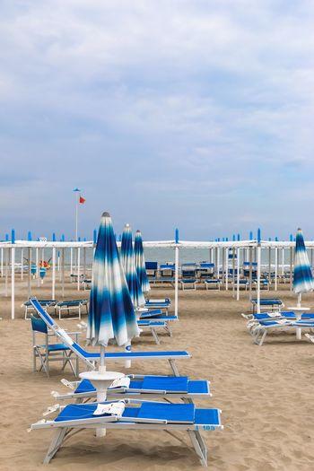 Empty beach, Italy, Riccione Italy. Riccione Italy Emiliaromagna Rimini Riccione Resort Sand Canopy Sunshade Umbrella Chaise Lounge Sunbed Beach Sky Sand Sea Nature Cloud - Sky Blue Shore Sun Lounger Tranquility Day Outdoors No People Vacations Scenics