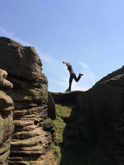 Full Length Side View Of Woman Balancing On Rock Formation Against Sky At Stanage Edge