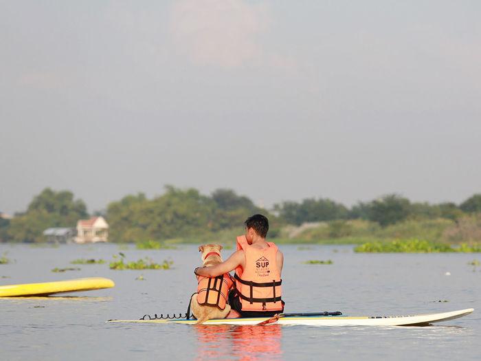 Men sitting on boat in lake against sky